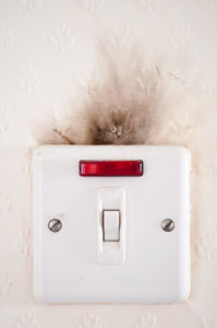 Photograph capturing the damage caused to an electrical point by faulty wiring.